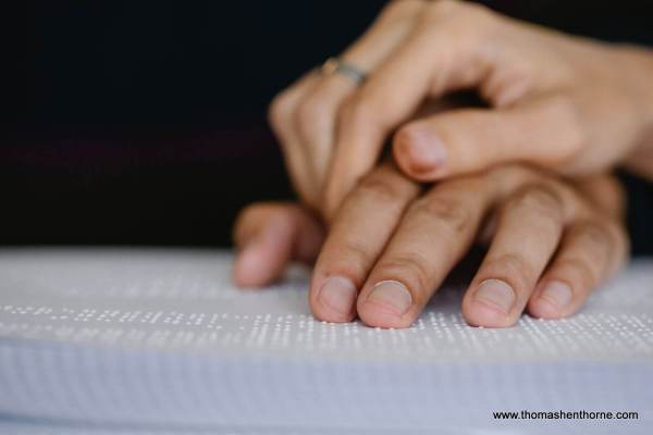 Photo of two people holding hands on a braille book