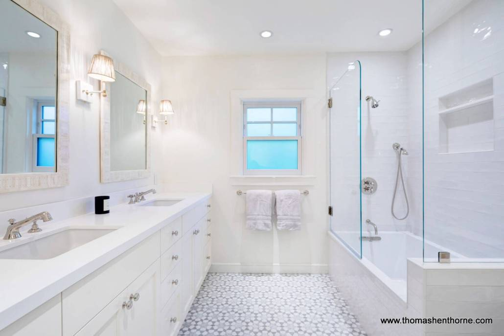 bathroom with dual sinks and glass enclosed shower tub