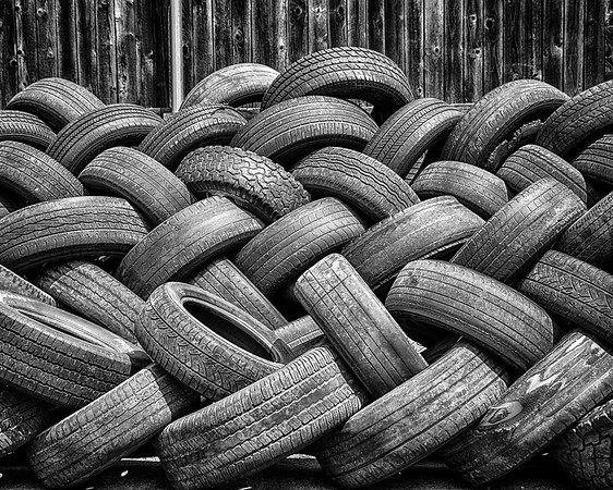 A pile of neatly arragned tires outside of a tire shop in Norman, OK.