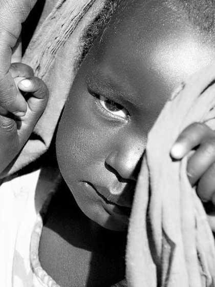 Flüchtling in Otash, Sudan. Kinderhände werden von einer Frauenhand gehalten. Das Kind ist sehr traurig. © Tom Rübenach