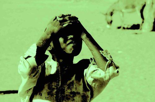 Ein Junge aus einem Flüchtlingslager verschränkt seine Arbe auf dem Kopf. Das Bild ist in grün gehalten. Foto © Tom Rübenach