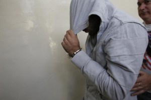 Israeli border policeman covers his head as he arrives at a remand hearing at the Magistrate Court in Jerusalem