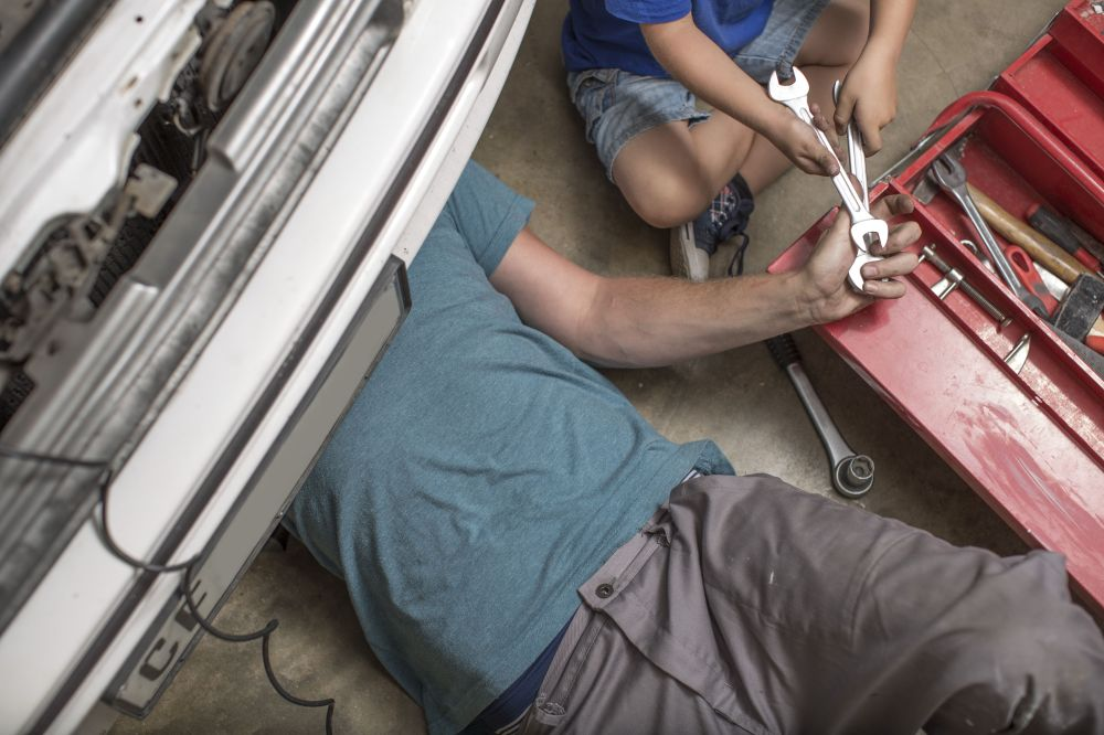medium resolution of son helping father in home garage working on car