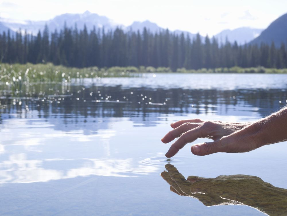 medium resolution of person s finger touching surface of mountain lake