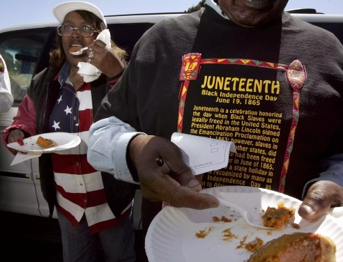 Woman wearing American flag shirt and eating next to man wearing shirt about Juneteenth and eating