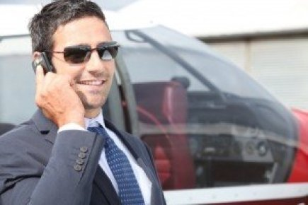 Businessman using a cellphone next to his private plane