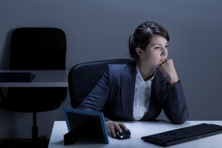 Woman Working Alone in Office at Night