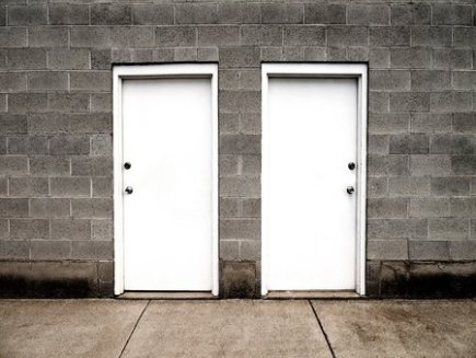 Two White Doors on a Gray Brick Wall Illustrating Choices