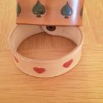 two leather cuffs sporting playing card motifs