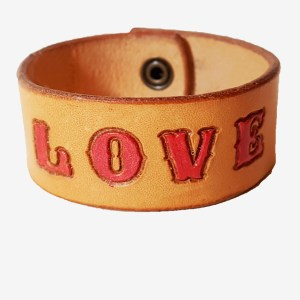 a cuff with the word love picked out in red on a natural tan background