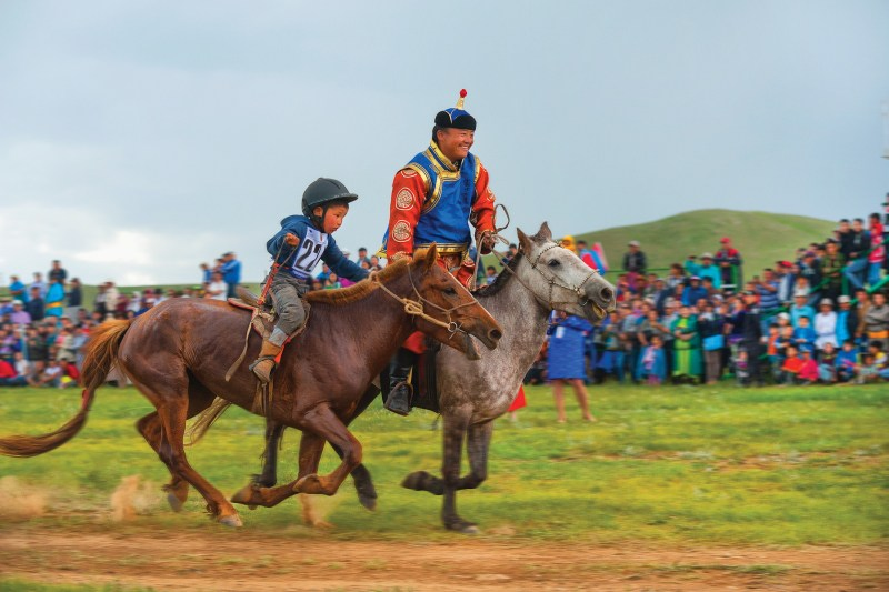 Man and child participate in traditional horse race at Naadam festival, Mongolia