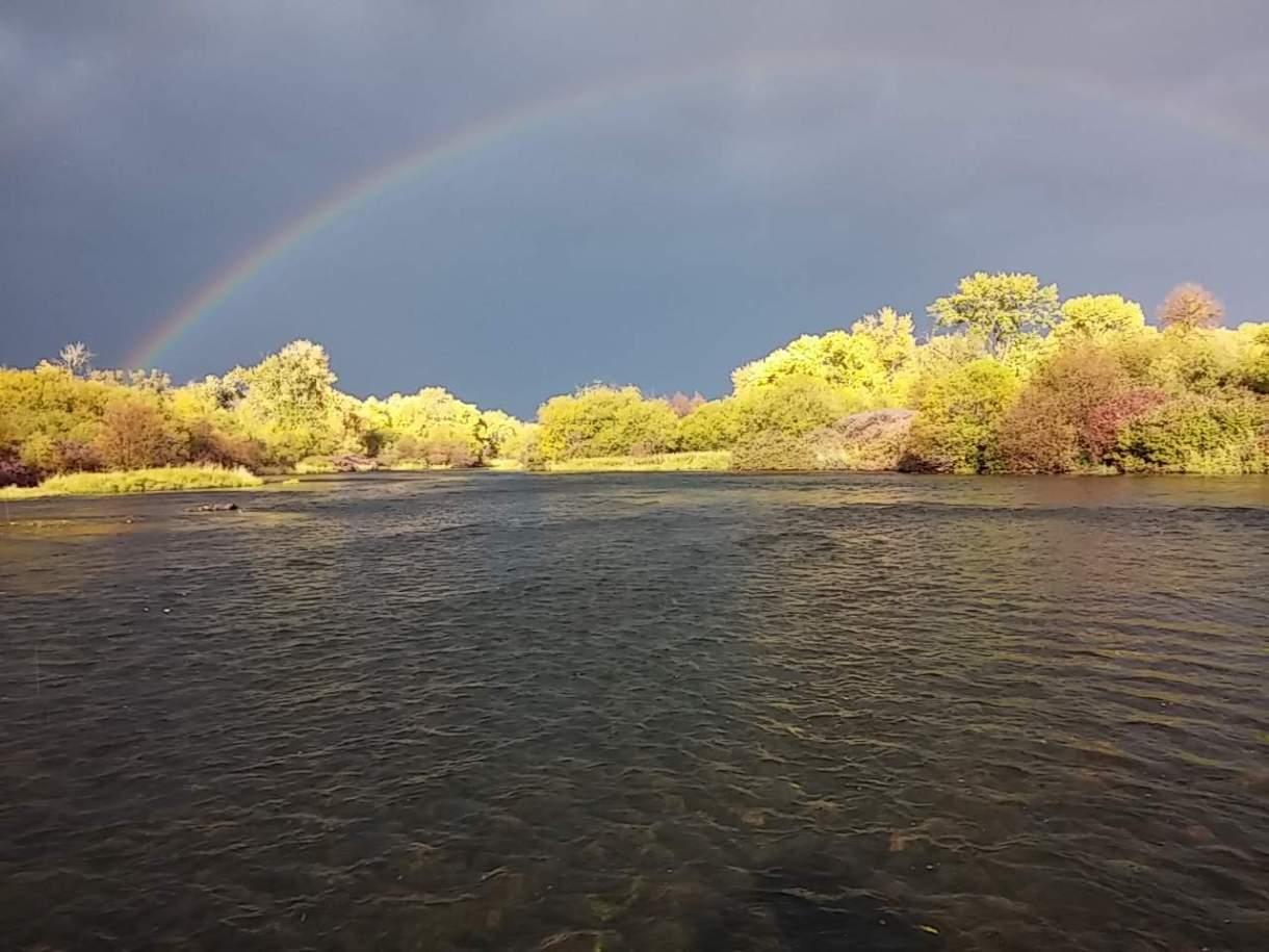 Photo of clouds and rainbow over Henry's Fork.