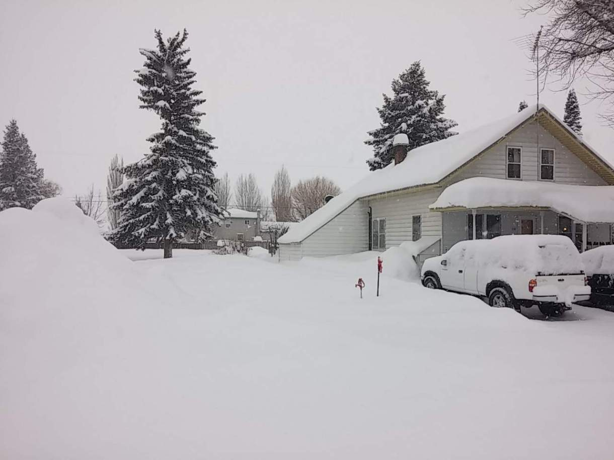 Photo of yard and driveway with a lot of snow.