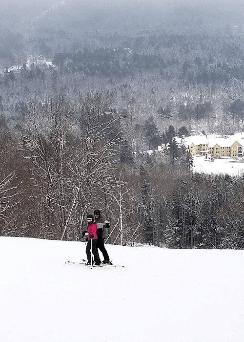 Two skiers standing on an incline overlooking the valley below where Jackson Gore Lodge is located at Okemo Mountain ski resort Vermont
