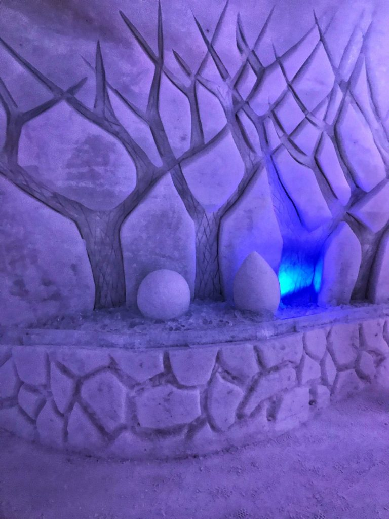 Purple_lit_trees_sculpted_into_snowy_walls_of_hotel-de_glace_quebec_2019