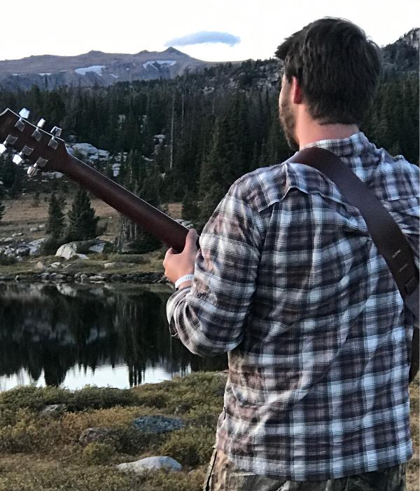 group travel Austin adventures tour guide playing guitar on beartooth pass Montana