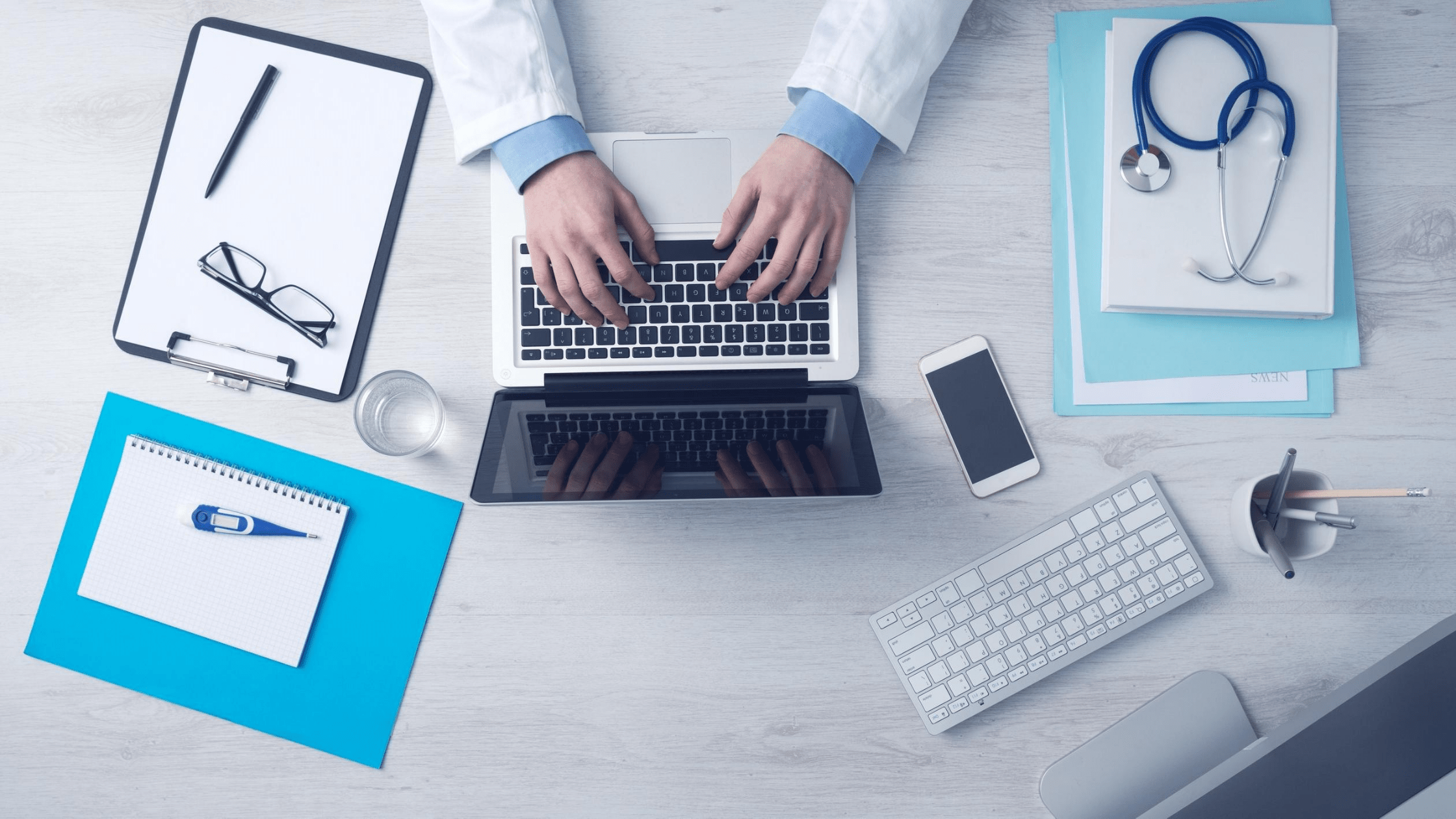 Doctor typing on laptop with notes all around him.