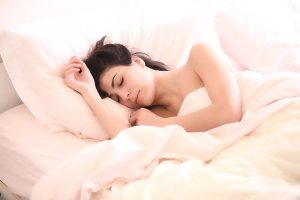 White woman with dark hair sleeping on a bed of white sheet, white pillowcase underneath a white comforter.