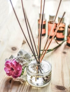 Aromatherapy sticks in a small glass jar with oil. 4 bottles of oil in the background. 2 flowers, one pink one white next to the bottle.