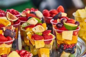 Fruit cups with stawberries, bananas, grapes, blueberries and limes