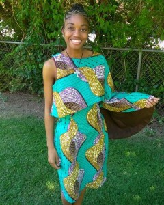 Netert Aset in a teal, yellow and purple print African dress.