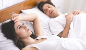 Young woman suffering from insomnia, husband sleeping aside
