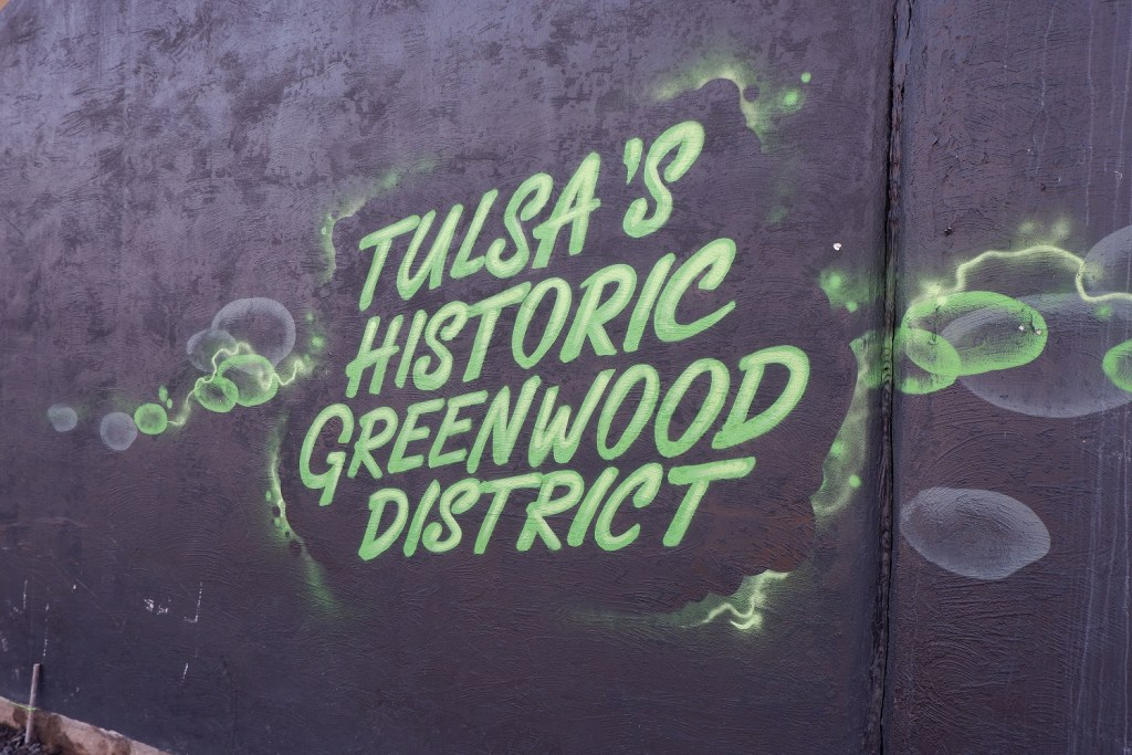 Tulsa's Historic Greenwood District Sign spray painted on wall in Greenwood District.