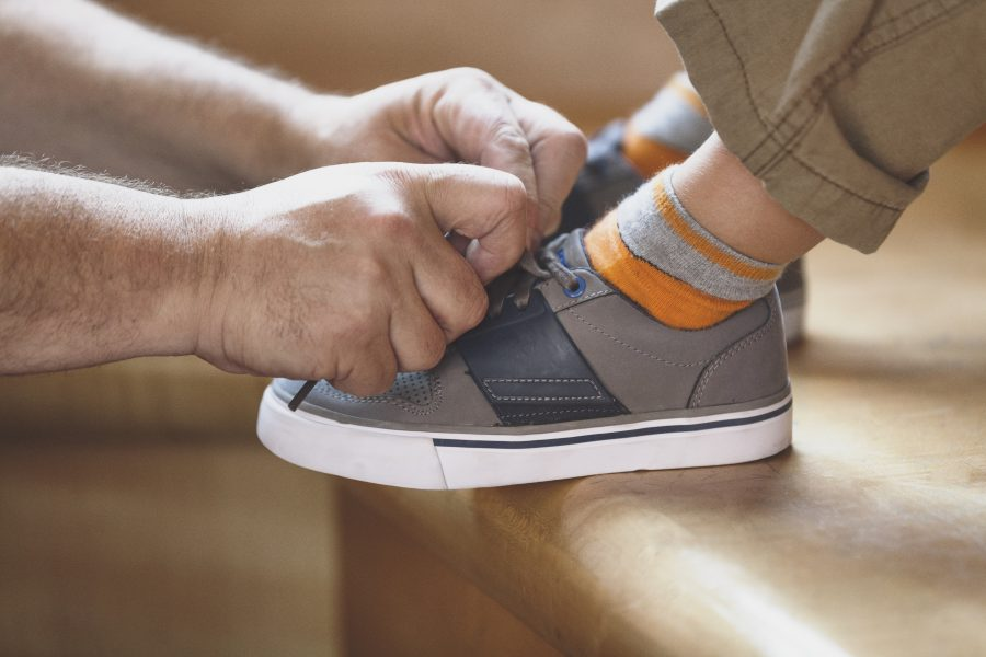 Father helping to tie his son's shoes