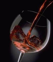 Bicchiere dove viene versano del vino rosso