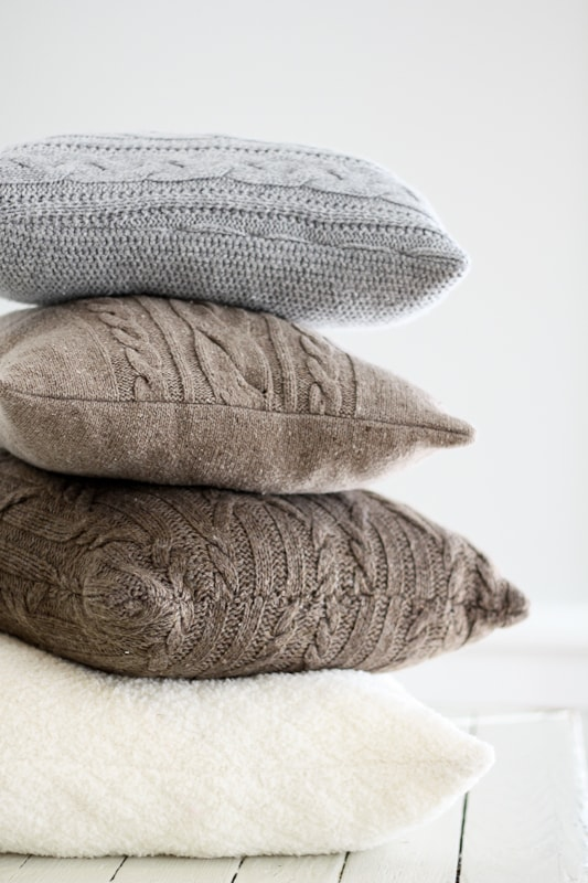 Cozy up your home with re-purposed sweater pillows - plus the key to avoiding wavy seams when sewing with knitted fabric.