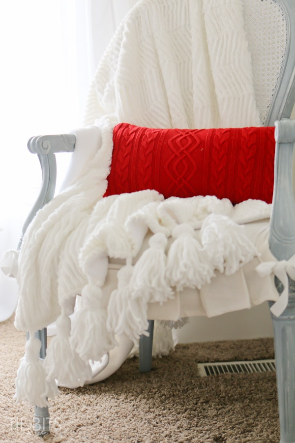 Tassel Throw Blanket DIY - Instructions for how to make your own tassels from yarn and how to sew them into fabric to make a one of a kind throw blanket.