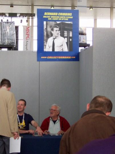 Bernard Cribbins sitting underneath his poster