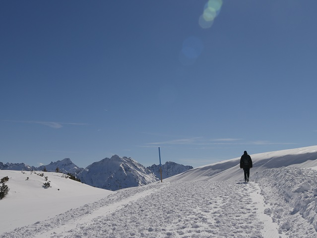 Wanderer im Schnee vor Berggipfeln