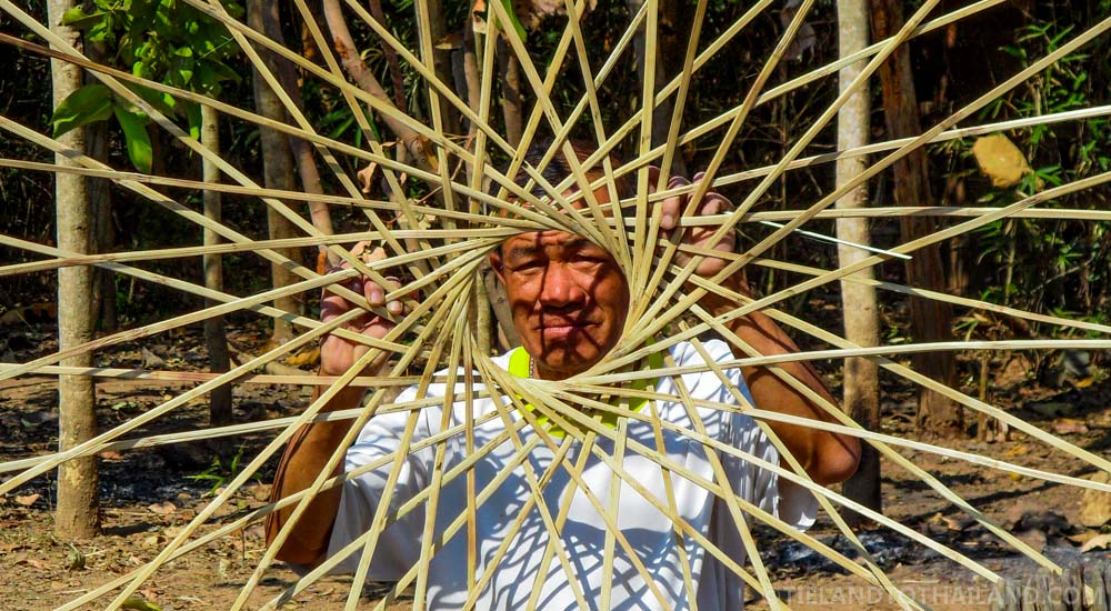 Isaan man, weaving fish-catching baskets