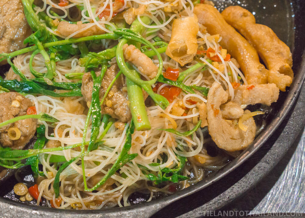 Thai-Chinese stir fry with morning glory, fried mushrooms, and thin rice noodles