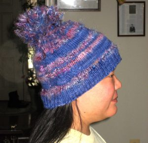 Knitted funky hat with pom pom, side view