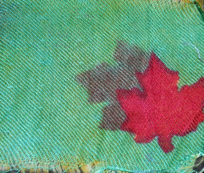 "fuchsia fiber-reactive dye, then stenciled again with red and yellow acid dyes.  Because it is a 3-1 twill with the tencel side up, the fiber-reactive maple leaf is dominant and the acid dye appears as a ""ghost""."
