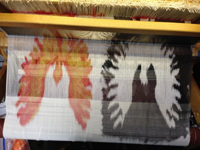 stenciled warp, being woven