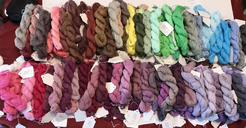 turquoise fuchsia sun yellow dye skeins, arranged by color