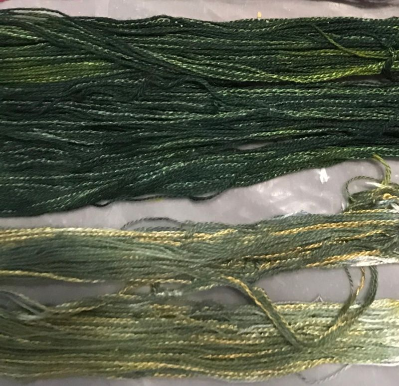 dark green skein on top, variegated yellow and medium green skein on bottom