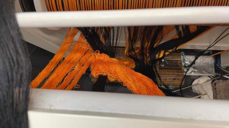 orange warp looped around black warp