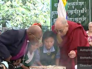Tutu und zwei Kinder helfen dem Dalai Lama seine Geburtstagskerzen aus zu blasen