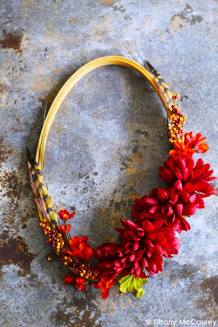A beaufitul, fall embroidery hoop wreath hangs on a stone wall with autumn colored flowers, berries and feathers.