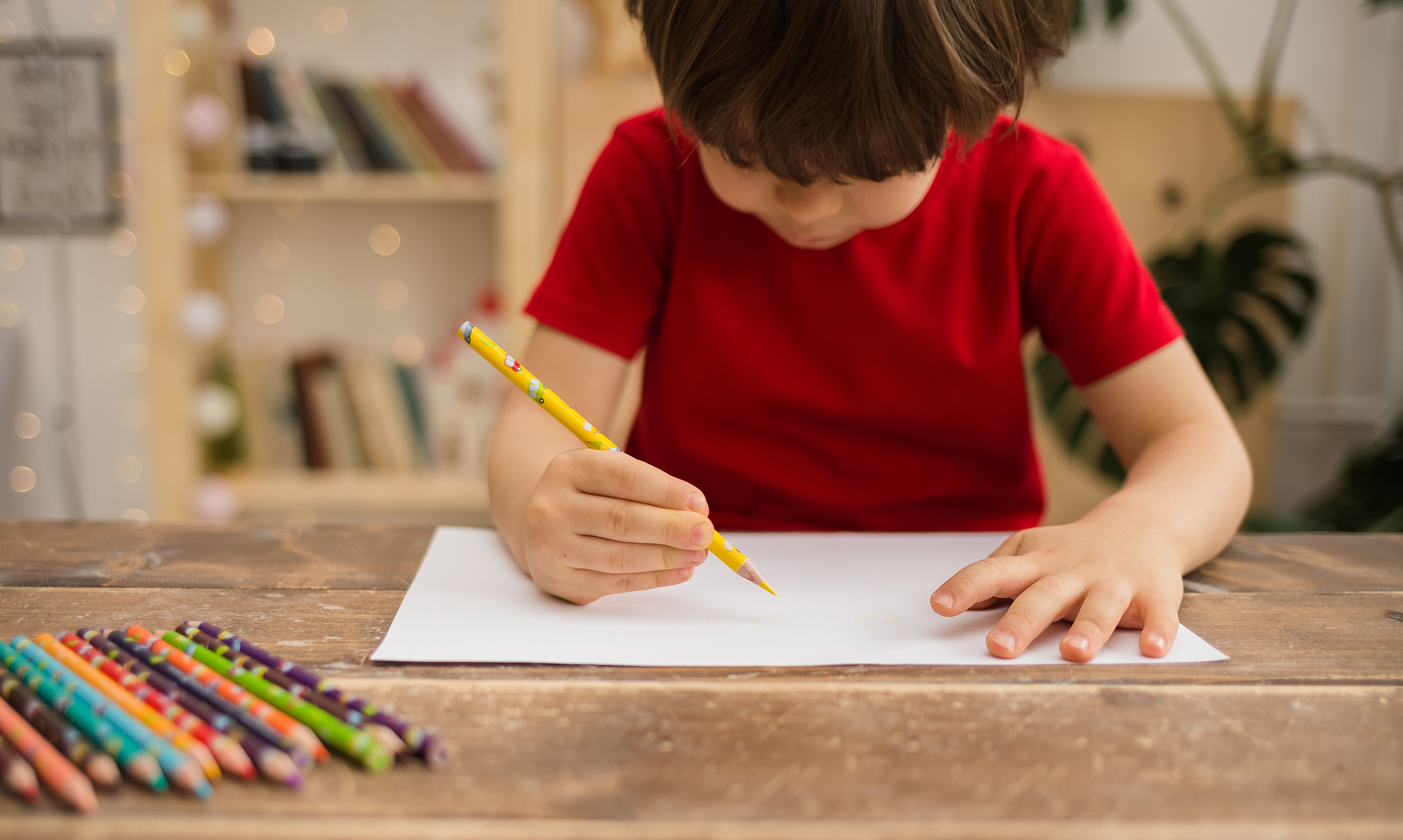 Toddler child practicing writing their name on a white piece of paper and colored pencil
