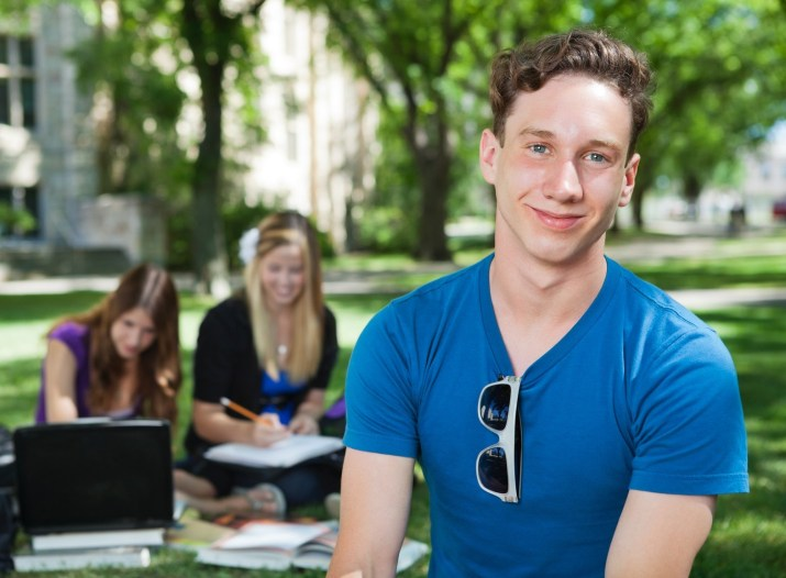 Portrait of happy college student with classmates in background