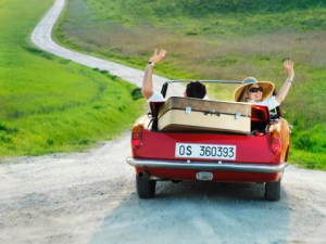 Couple driving convertible car in countryside, waving arms, rear view