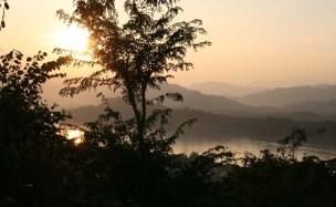 Aurinko laskee Mekongin ja vuorten taa Luang Prapangissa.