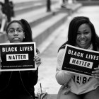 """Two black girls holding signs that say """"Black Lives Matter"""""""