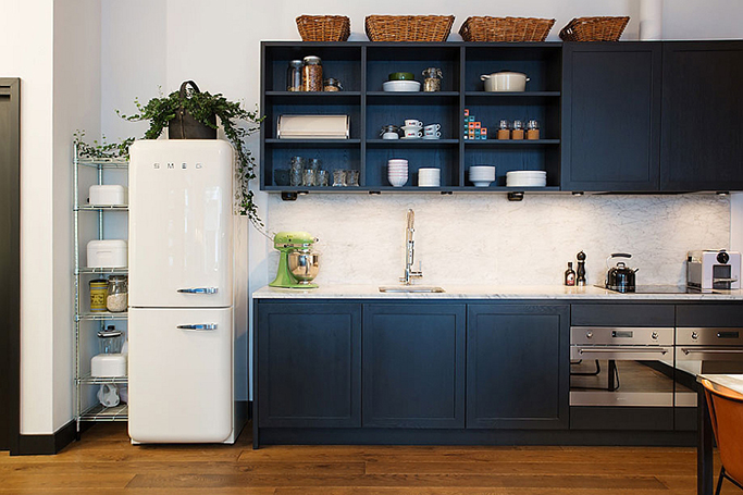 ergonomic-kitchen-with-navy-blue-cabinet-modern-appliances-and-small-refrigerator