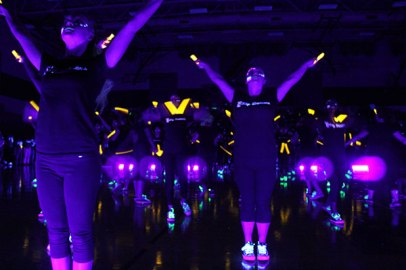 "TCHS Sky Dancers perform a glowing dance routine during the ""Blackout"" blacklight pep rally, Nov. 7, 2014. (Photo by The Creek Yearbook photographer Sabrina Trejo.)"